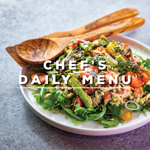 Chefs daily menu - bowl of fresh salad and serving spoon and fork