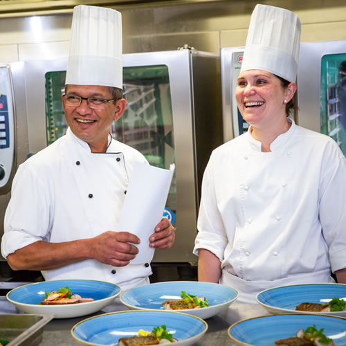 Food Preparation: Happy kitchen staff overseeing food